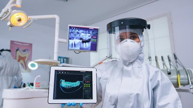 Dokter die digitale röntgenfoto's toont op tablet in tandartspraktijk met nieuw normaal, waarin de behandeling van tanden wordt uitgelegd. stomatologie die beschermend pak draagt tegen infectie met coronavirus wijzend op radiografie.