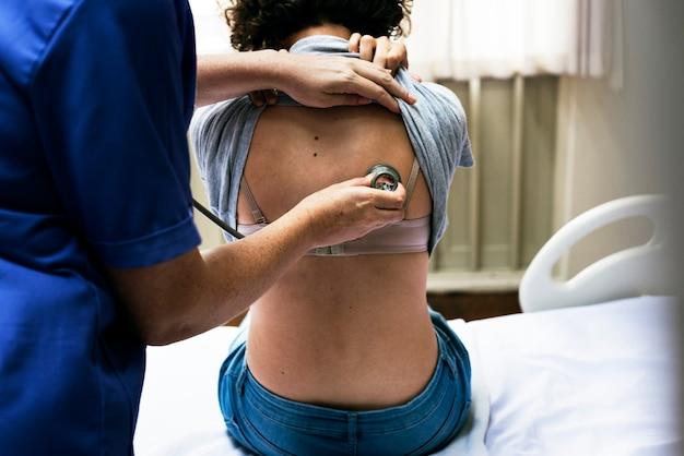 Dokter die een ademhaling van een patiënt controleert