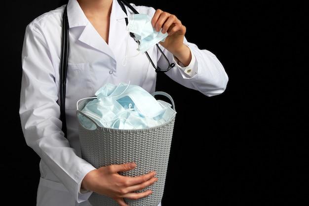 Dokter die een emmer vol gebruikte gezichtsmaskers vasthoudt en ze weggooit als symbool van het einde van de epidemie