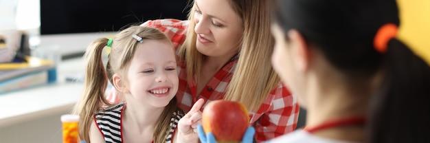 Dokter die een kleine meisjesfles geneeskunde en rode appel in kliniek aanbiedt