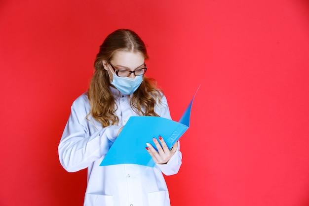 Dokter die gezichtsmasker draagt, opent en controleert de geschiedenis van de patiënt.