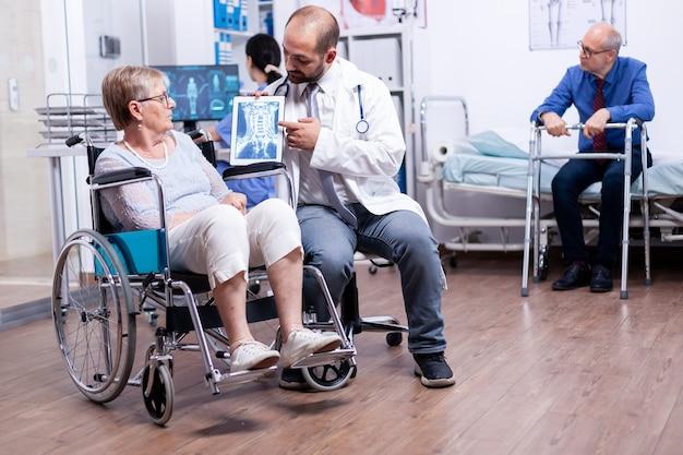 Dokter die hersenröntgenfoto toont van gehandicapte oudere senior vrouw in rolstoel