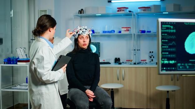 Dokter die hersenscan analyseert met behulp van tablet, onderzoekt de evolutie van de ziekte die in een neurologisch laboratorium werkt