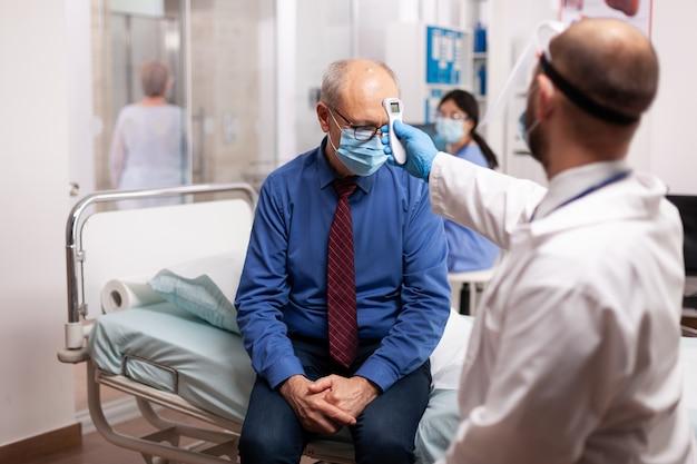Dokter die lichaamstemperatuur meet met digitale thermometer van zieke senior man met gezichtsmasker tijdens coronavirus