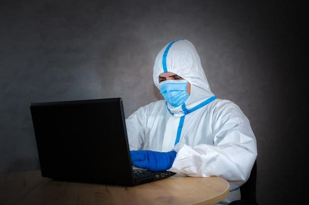 Dokter die medisch beschermend pak, medisch masker en handschoenen draagt die aan laptop werken. bescherming mers door virusepidemie. coronavirus (covid-19). gezondheidszorgconcept.