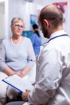 Dokter die medisch document vasthoudt terwijl hij spreekt met een oudere oude vrouw in de kliniekkast