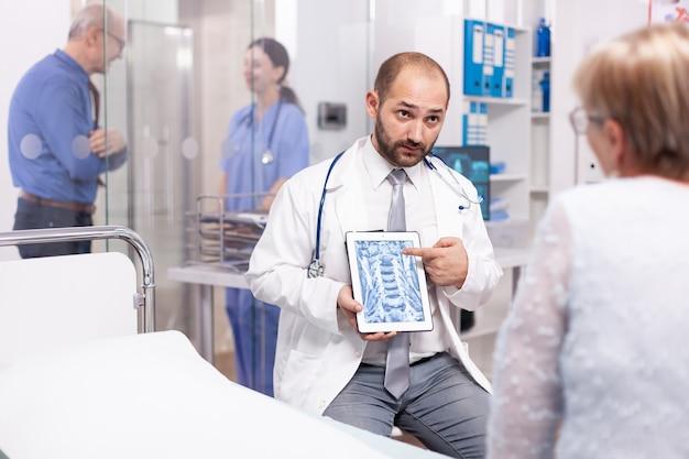 Dokter die radiologische scan toont aan senior patiënt na medische controle in de onderzoekskamer van het ziekenhuis