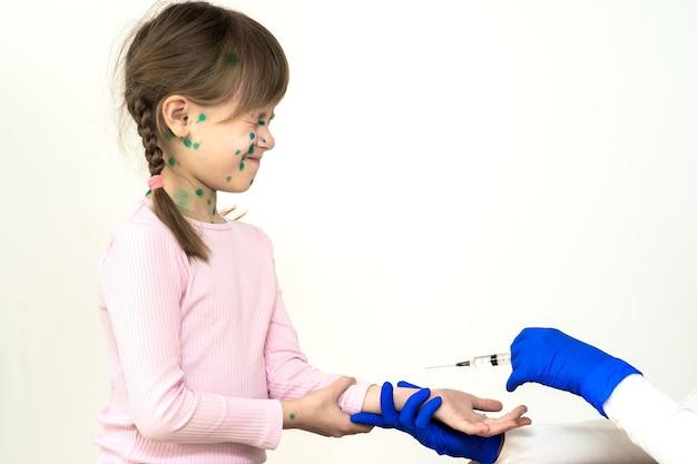 Dokter die vaccinatie-injectie maakt bij een bang kindmeisje dat ziek is van waterpokken, mazelen of rubellavirus.