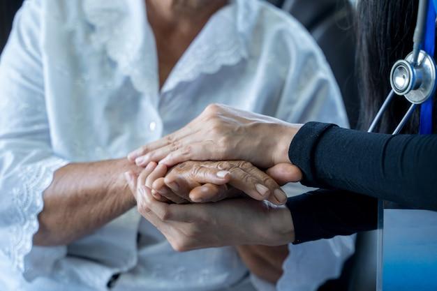Dokter die voor oudere vrouw in het ziekenhuis zorgt, samengesteld beeld van verpleegster die de hand van de patiënt vasthoudt, geriatrie ouderenzorg concept.