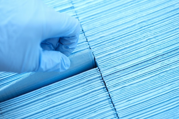 Dokter dient rubberen handschoenen in en trekt steriel wegwerpservet uit de verpakkingsclose-up