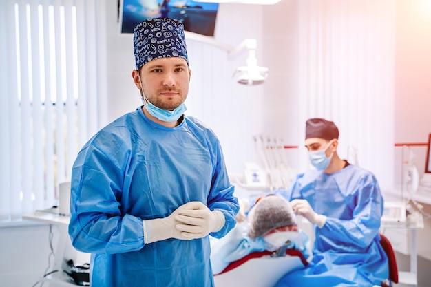 Dokter draagt blauwe jas die u uitnodigt naar het kantoor van de tandarts en camera met tandheelkundige stoel en patiënt in de.