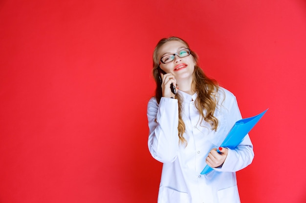 Dokter draagt een bril en houdt een blauwe map vast die tegen de telefoon praat.