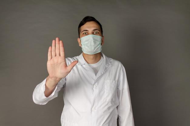Dokter draagt een masker om te beschermen tegen coronavirus en steekt zijn hand op