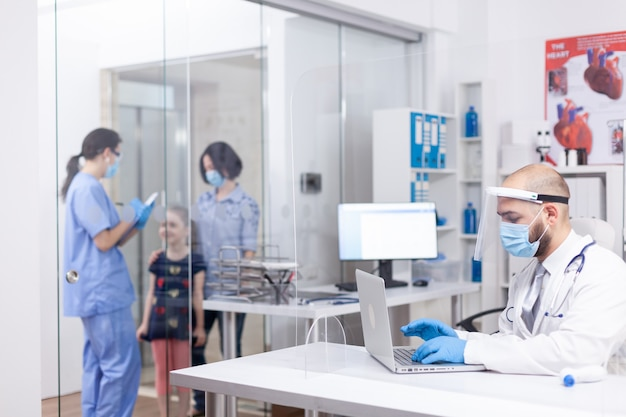 Dokter draagt gezichtsmasker tegen coronavirus in ziekenhuiskantoor en verpleegster in gesprek met patiënten