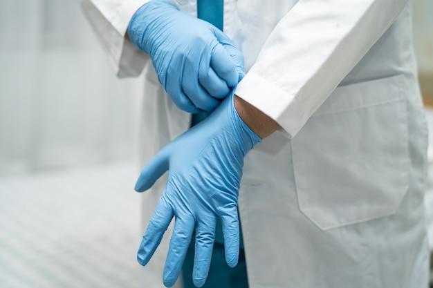 Dokter draagt handschoenen ter bescherming van het covid-19 coronavirus.