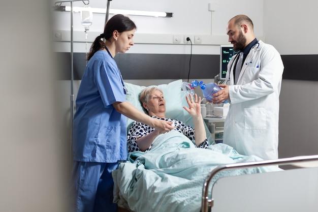 Dokter en medisch verpleegkundige haasten zich om oudere vrouw te helpen ademen