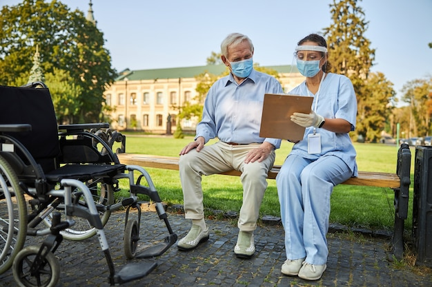 Dokter en oude man kijken naar ziektegeschiedenis