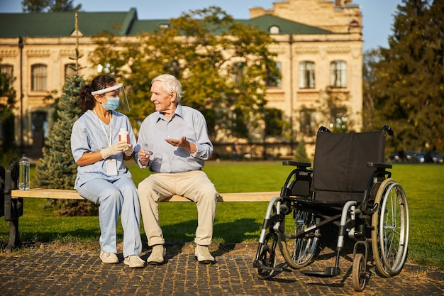 Dokter en oude man zitten buiten het verpleeghuis