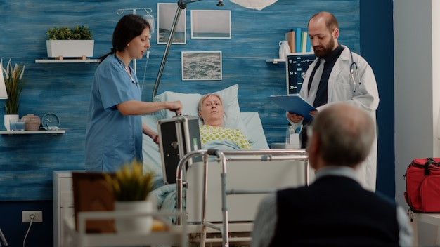 Dokter en verpleegster doen controlebezoek voor zieke patiënt in ziekenhuisbed