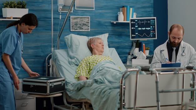 Dokter en verpleegster doen medische controle met gepensioneerde vrouw