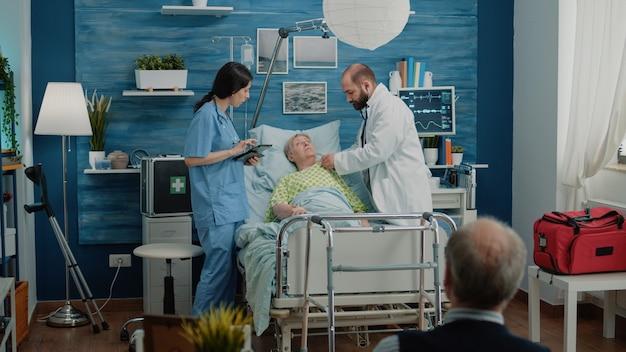 Dokter en verpleegster raadplegen gepensioneerde vrouw die in ziekenhuisbed ligt