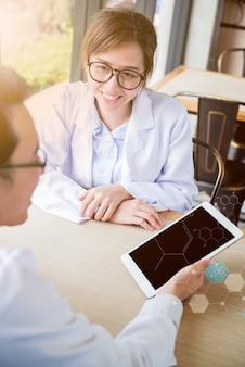 Dokter en wetenschapper ontmoeten elkaar, werken aan internet voor nieuwe technologie