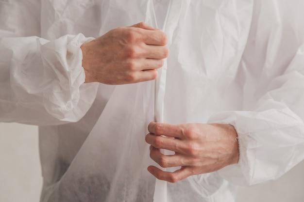Dokter epidemioloog zet op witte beschermende overall, maakt een rits vast, handen close-up