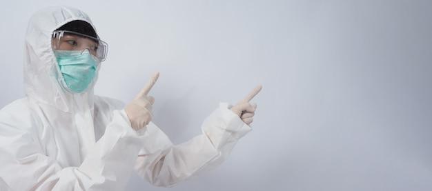 Dokter gebaar aziatische vrouw arts in ppe pak of persoonlijke beschermingsmiddelen gebaren en wijzen. witte medische rubberen handschoenen. brilbril en groen n95-masker om pandemisch coronavirus te beschermen.