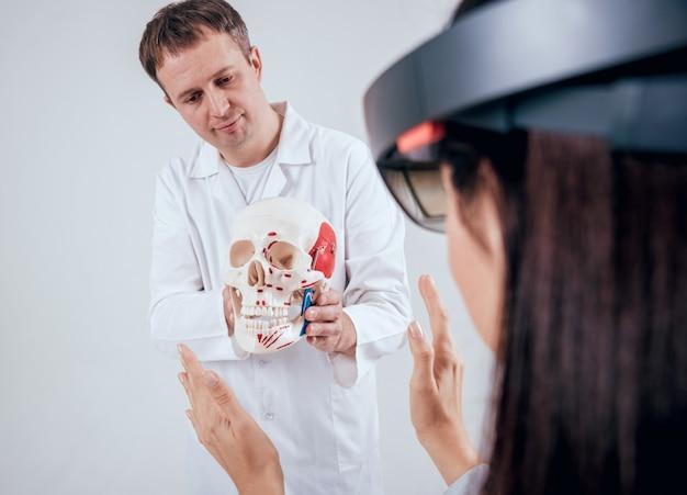 Dokter gebruikt augmented reality-bril en menselijk skelet voor het lesgeven aan studenten