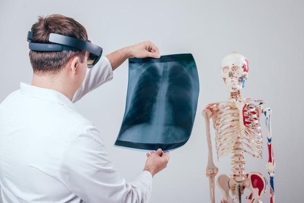 Dokter gebruikt augmented reality-bril om röntgenfilm met menselijk skelet te onderzoeken