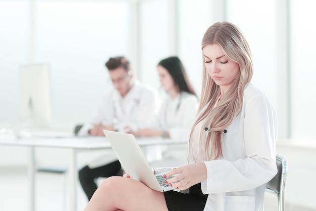 Dokter gebruikt een laptop om met documenten te werken .photo met kopieerruimte