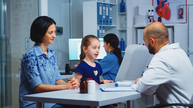 Dokter geeft high five met kleine patiënt in medisch kantoor. gezondheidszorgbeoefenaar, arts, specialist in geneeskunde die medische diensten verleent consultatie diagnostische behandeling in het ziekenhuis.