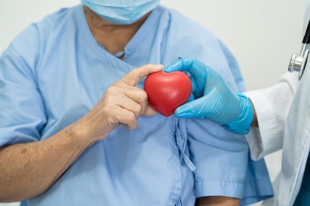 Dokter geeft rood hart aan aziatische senior vrouw patiënt gezond sterk medisch
