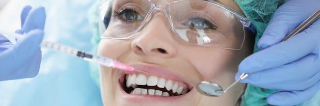 Dokter geeft vrouw een close-up van een verdovende injectie