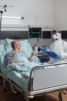Dokter gekleed in pbm-pak met gezicht in verlegenheid gebracht in gesprek met senior patiënt, liggend in bed met zuurstofmasker tijdens uitbraak van coronavirus
