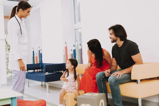 Dokter greets kid in kliniek familie bij de receptie.