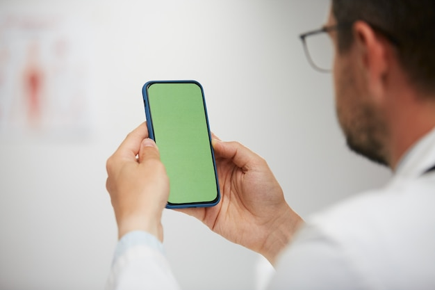 Dokter groen scherm smartphone, senior arts met behulp van chroma key telefoon zitten in medische kabinet in witte jurk en gassen
