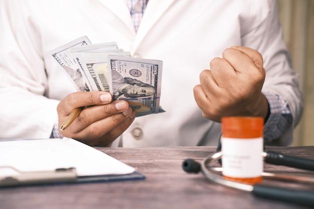 Dokter hand contant geld tellen met pil container op tafel