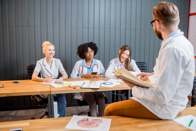 Dokter heeft een les met studenten die chatten met smartphones die aan het bureau zitten in het moderne klaslokaal