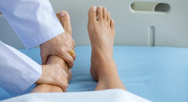 Dokter houdt benen patiënt op bed in het ziekenhuis en controleert het zenuwstelsel voor genezing en behandeling. concept van guillain-barre-syndroom en gevoelloze handenziekte of vaccinbijwerking. Premium Foto