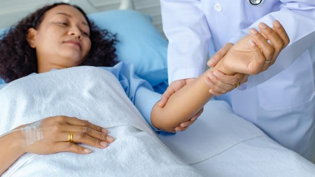 Dokter houdt de hand van aziatische vrouwelijke patiënt op bed in het ziekenhuis en controleert het zenuwstelsel voor genezing en behandeling. concept van guillain-barre-syndroom en gevoelloze handenziekte of vaccinbijwerking.
