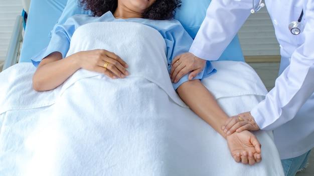 Dokter houdt de hand van de patiënt op bed in het ziekenhuis en controleert het zenuwstelsel voor genezing en behandeling. concept van guillain-barre-syndroom en gevoelloze handenziekte of vaccinbijwerking.