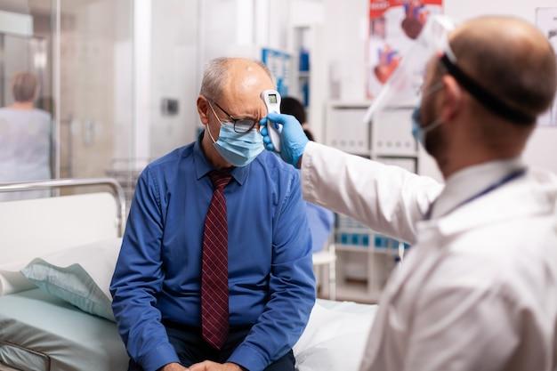 Dokter houdt digitale thermometer op het voorhoofd van de patiënt en controleert de temperatuur tijdens een pandemie van het coronavirus