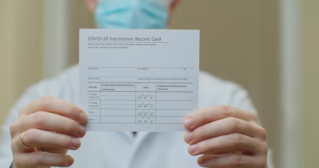 Dokter houdt een vaccinatierecordkaart en injectieflacons voor het coronavirus vast. paspoort van immuniteit tegen het coronavirus in handen van een mannelijke arts.