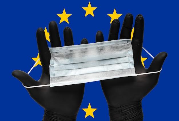 Dokter houdt gezichtsmasker in handen in zwarte medische handschoenen op achtergrondkleuren vlag van de europese unie eu. pandemische verzekering coronavirus, grippe, door de lucht overgedragen ziekten, griep. menselijk ademhalings medisch masker.