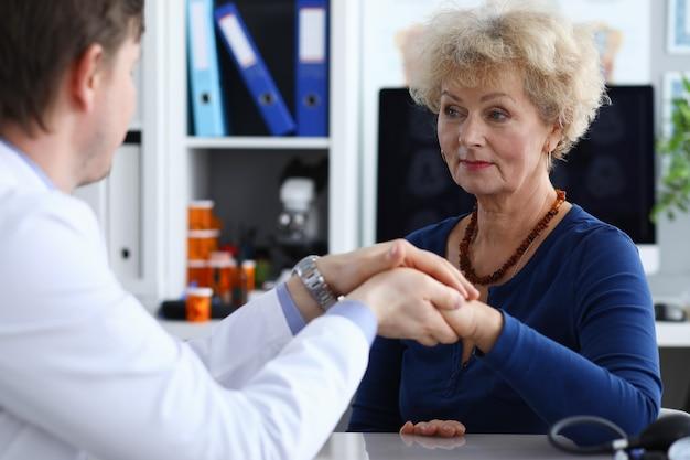 Dokter houdt handen van oudere vrouw in medische kantoor