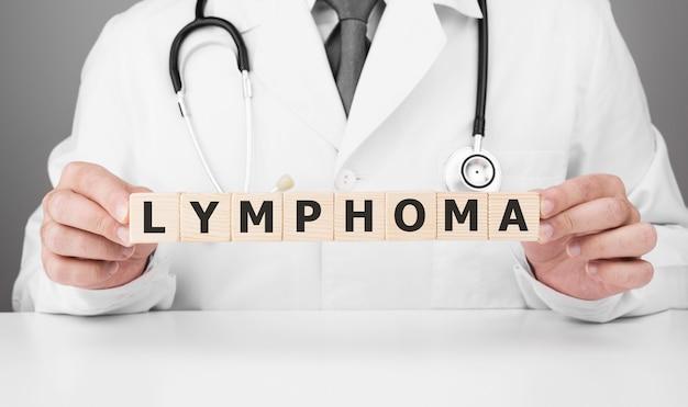 Dokter houdt houten blokjes in zijn handen met tekst lymfoom