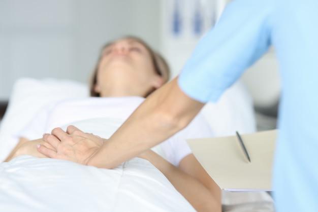 Dokter houdt liggende patiënt met de hand op ziekenhuisbed. intramuraal onderzoek concept