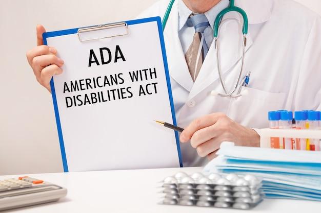 Dokter houdt papier met american disabilities ada, stethoscoop en pillen op tafel