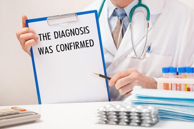 Dokter houdt papier met inscriptie de diagnose is bevestigd, een stethoscoop en pillen op tafel